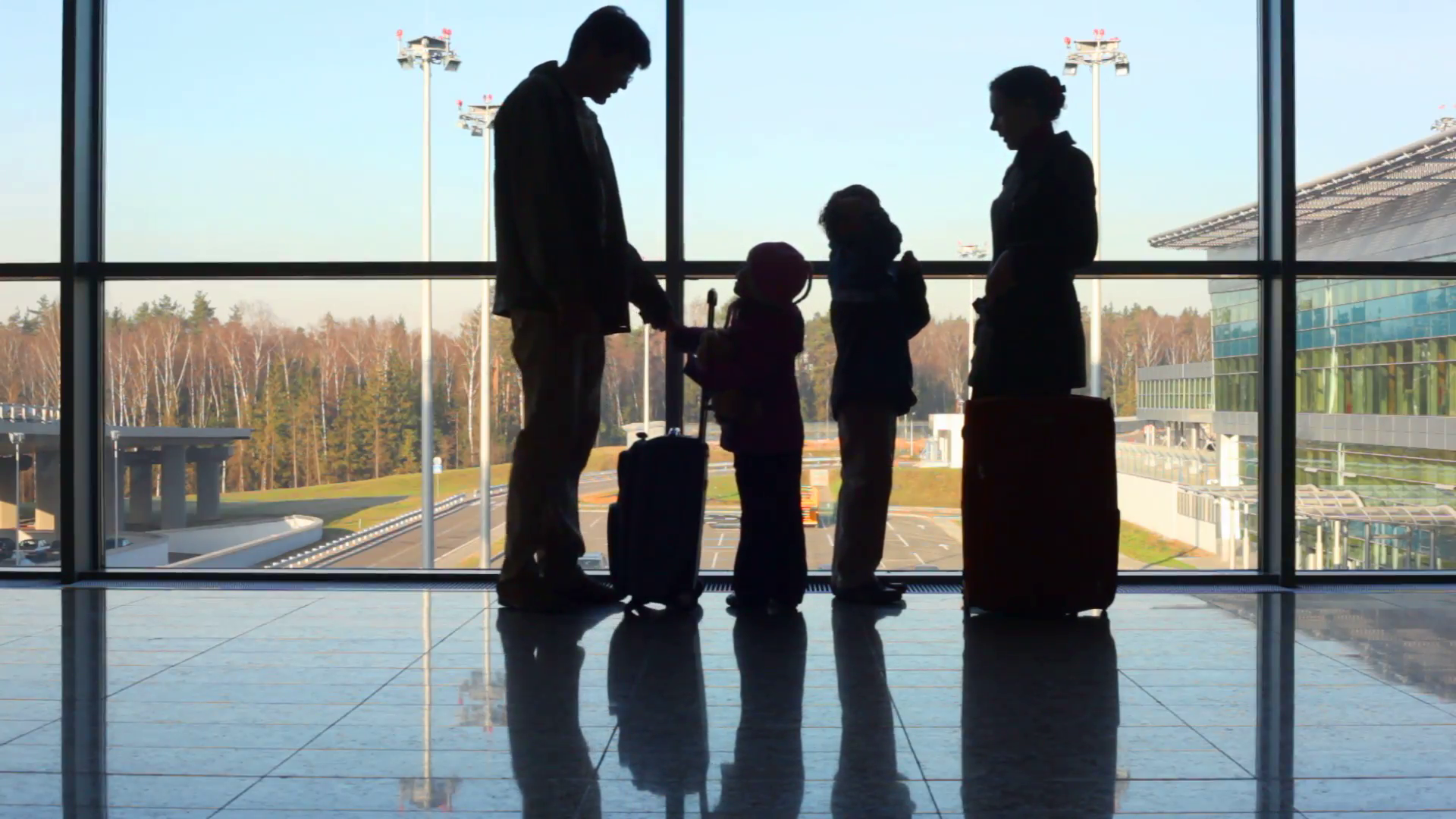 family-stands-against-window-at-airport_7khajhud__F0000